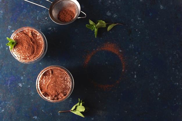Dwie porcje tiramisu przyozdobione kakao i miętą