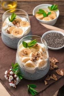 Dwie porcje zdrowego naturalnego deseru z nasionami chia na mleku roślinnym z bananem, orzechami i miodem na brązowej, drewnianej ścianie. widok z boku, pionowy.