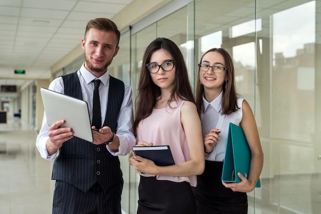 Dwie poważne bizneswoman i jeden mężczyzna pokazują dokument i rozmawiają o błędzie podwładnego na korytarzu biura. koncepcja spotkania