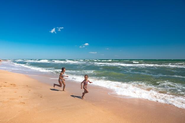 Dwie pozytywne dziewczynki biegają wzdłuż piaszczystej plaży w słoneczny, ciepły letni dzień. pojęcie aktywnego wypoczynku dziecka a zdrowie dzieci. copyspace
