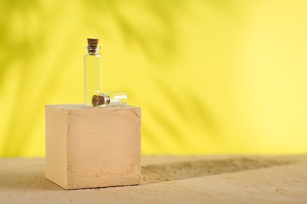 Dwie przezroczyste butelki w kostce z teksturą na beżowej powierzchni na żółto z cieniami liści.
