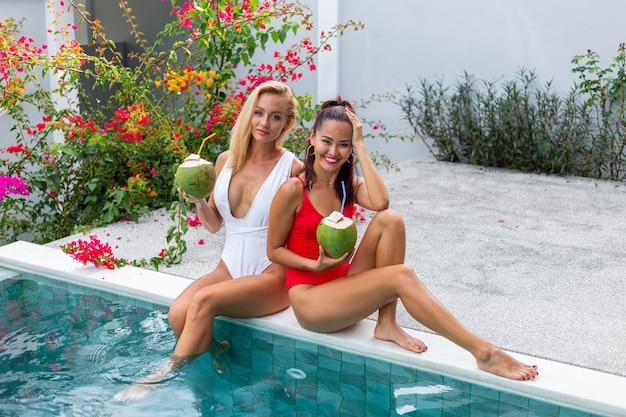 Dwie przyjaciółki azjatyckie i rasy kaukaskiej z makijażem na brzegu basenu w willi przyjaciółki z kokosami na wakacjach przy niebieskim basenie i drzewie kwiatowym