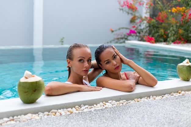 Dwie przyjaciółki kobieta azji i kaukaski z makijażem w basenie w willi