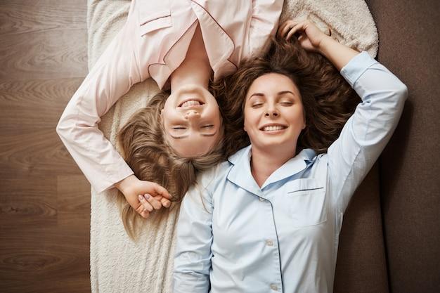 Dwie przyjaciółki leżące na sofie w wygodnej piżamie z zamkniętymi oczami, uśmiechnięte i odprężające