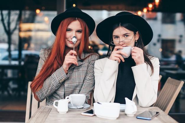 Dwie przyjaciółki picia kawy w kawiarni
