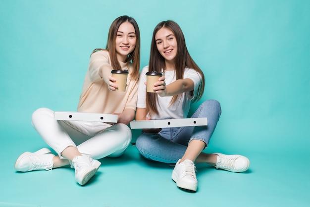Dwie przyjaciółki siedzące na podłodze piją kawę i jedzą pizzę na białym tle na turkusowej ścianie