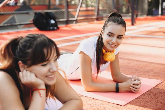 Dwie przyjaciółki śmiejąc się po wykonaniu ćwiczeń odchudzających na świeżym powietrzu w parku sportowym.