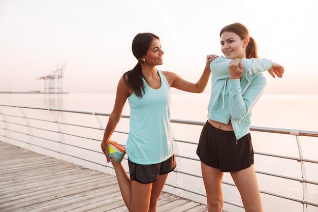 Dwie przyjaciółki sportowe kobiety na zewnątrz na plaży wykonują ćwiczenia sportowe