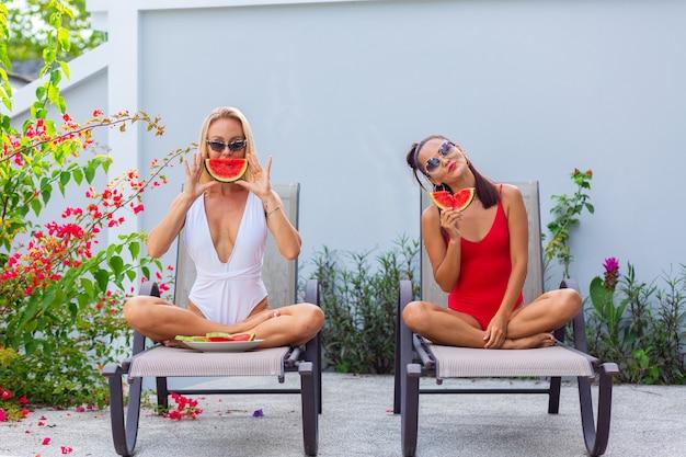 Dwie przyjaciółki w azjatyckich i kaukaskich strojach kąpielowych na leżaku przy basenie w willi o arbuzie wakacje w krajach tropikalnych świeże owoce