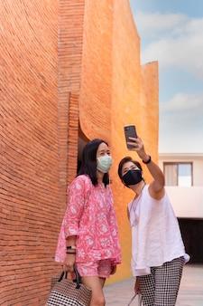 Dwie przyjaciółki w maskach ochronnych robią sobie selfie za pomocą telefonu komórkowego