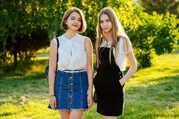 Dwie przyjaźnie najlepsze dziewczyny uczennice pozują w parku