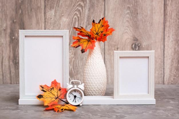 Dwie puste ramki na stojaku, wazon z pomarańczowymi liśćmi klonu i biały stojak na budzik na stole. kolorystyka biało-pomarańczowo-beżowa