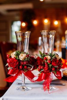 Dwie puste szklanki ślubne, ozdobione zielenią, czerwonymi różami i wstążką, stojące na stole bankietowym