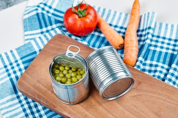 Dwie puszki gotowanego zielonego groszku, warzywa i obrus.