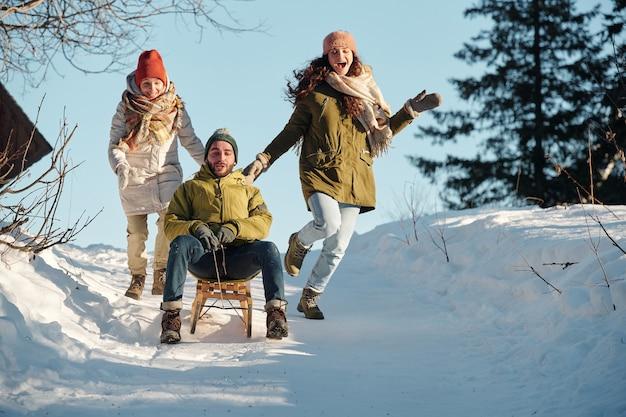 Dwie radosne dziewczyny w odzieży zimowej biegnące za młodym mężczyzną na saniach zjeżdżających ze wzgórza wśród zasp w lesie podczas zabawy w zimowy dzień