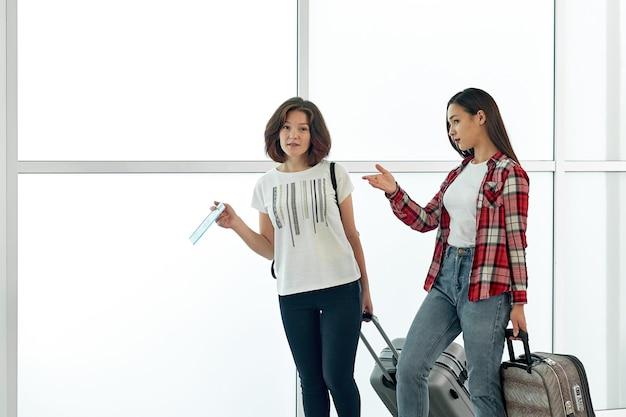 Dwie radosne kobiety z bagażem i biletami na lotnisku przed odlotem. rozmowa i śmiech przed wakacjami i podróżą.