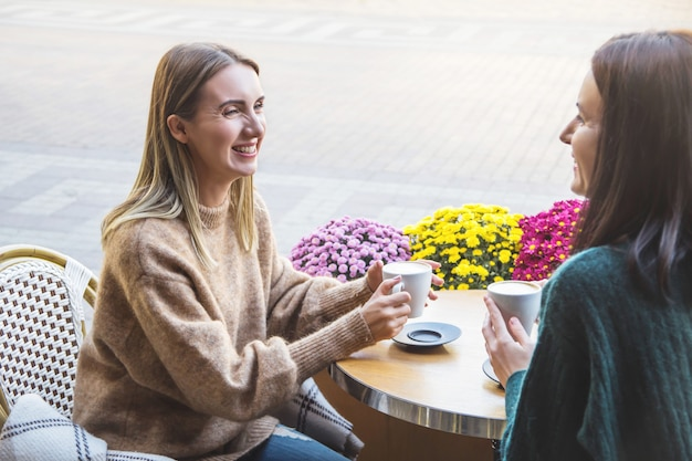Dwie radosne koleżanki piją cappuccino w kawiarni na ulicy miasta.