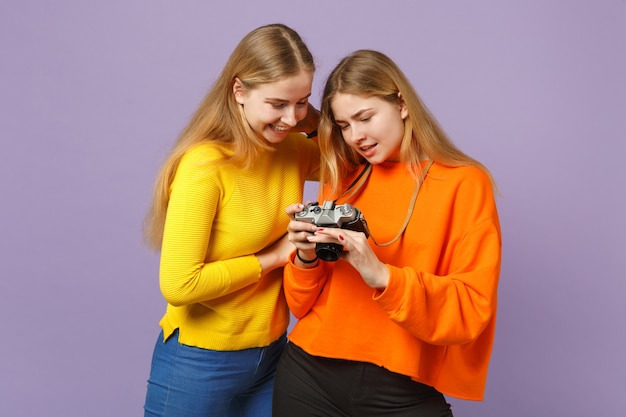 Dwie radosne młode bliźniaczki blond siostry dziewczyny w żywe kolorowe ubrania trzymając aparat retro vintage na białym tle na fioletowej ścianie niebieski. koncepcja życia rodzinnego osób.