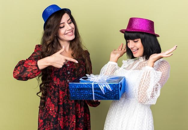 Dwie radosne młode dziewczyny imprezowe w kapeluszu imprezowym, jeden trzymający i wskazujący na pakiet prezentowy, patrzący na swoją przyjaciółkę, inną dziewczynę pokazującą puste ręce patrzące na pakiet na białym tle na oliwkowozielonej ścianie