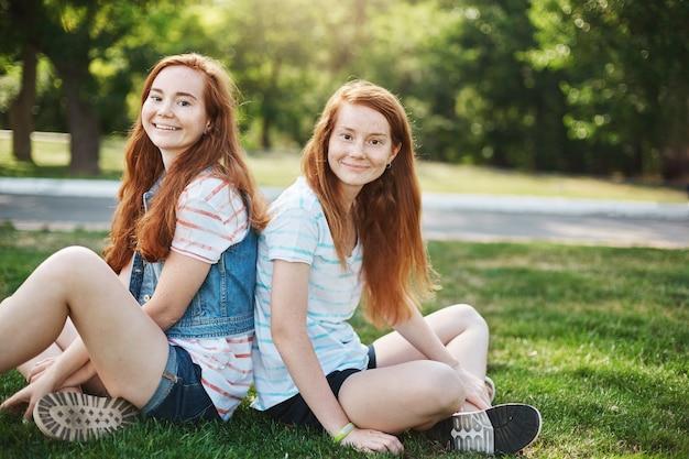 Dwie radosne młode kobiety o rudych włosach siedzą ze skrzyżowanymi nogami na trawie i patrzą z beztroskim i radosnym wyrazem twarzy, spędzają czas, rozmawiają z kumplami. koncepcja emocji