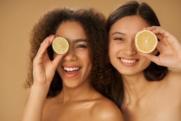Dwie radosne młode kobiety rasy mieszanej wyglądające na podekscytowane, zakrywające oczy cytryną i limonką przeciętą na pół