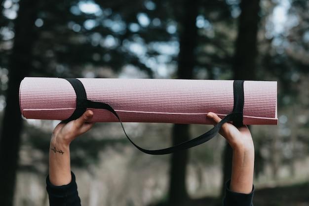 Dwie ręce chwytające matę do jogi w powietrzu w lesie koncepcja relaksu