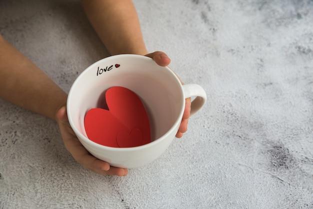Dwie ręce dziecka trzymając czerwone papierowe serca.