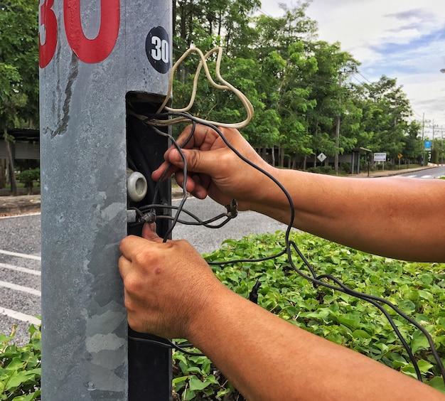 Dwie ręce elektryka naprawy drutu elektrycznego w słupie lampy.