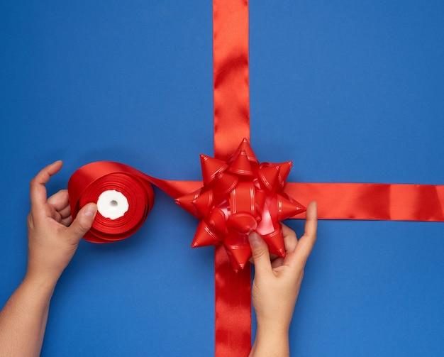 Dwie ręce kobiece zawiązują czerwoną wstążką jedwabną na niebieskim pudełku, pakowanie prezentów