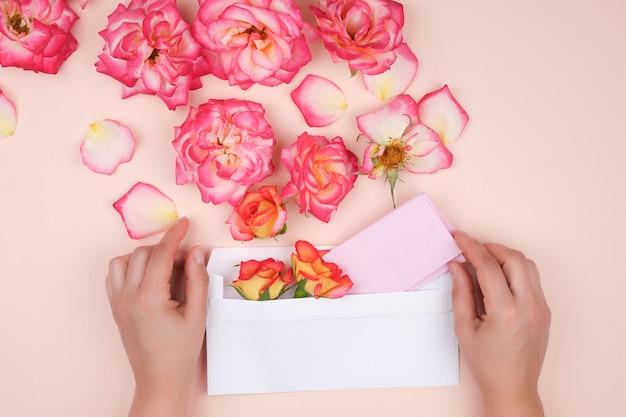 Dwie ręce kobiety trzymają białą papierową kopertę