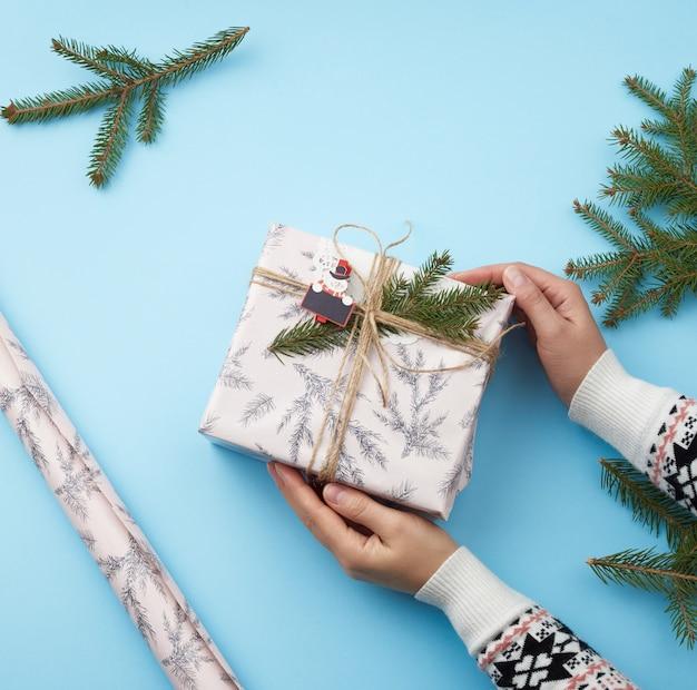 Dwie ręce kobiety trzymającej prezent zawinięty w świąteczny papier pakowy