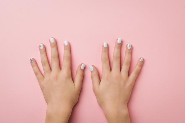 Dwie ręce kobiety z makijażem na różowej powierzchni