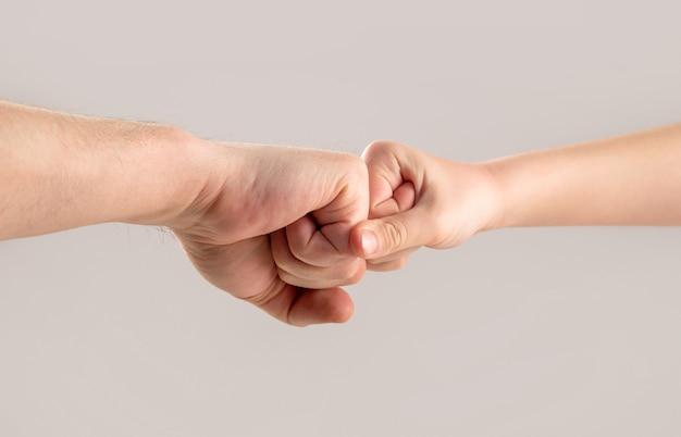 Dwie ręce mężczyzny i dziecka. ojciec i syn dotykając pięściami. stary ma