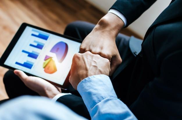 Dwie ręce młodego człowieka biznesu wpadające razem i statystyki finansowe wyświetlane na ekranie tabletu mobilnego