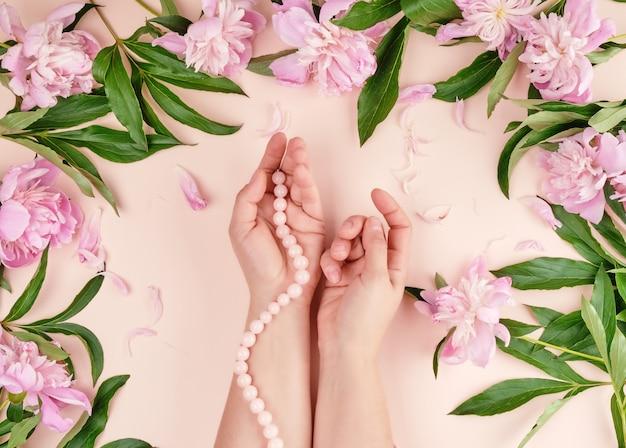 Dwie ręce młodej dziewczyny o gładkiej skórze i bukietem różowych piwonii na kwiatach brzoskwini