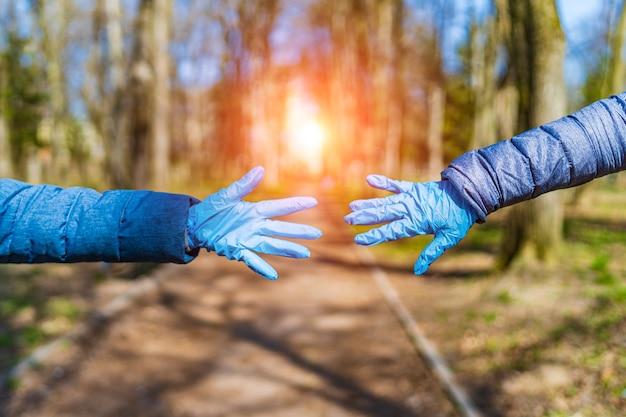 Dwie ręce próbują trzymać się nawzajem w tle parku. pojęcie pandemii, kwarantanny, zapobiegania wirusom, chorobom.