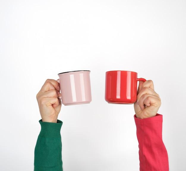 Dwie ręce trzyma ceramiczne kubki