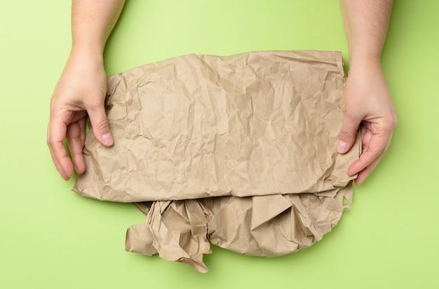 Dwie ręce trzyma kawałek zmiętego brązowego papieru na białym tle