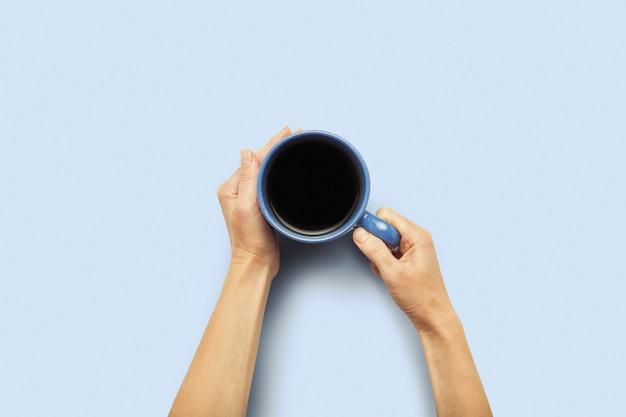 Dwie ręce trzyma kubek z gorącą kawą na niebieskim tle. koncepcja śniadanie z kawą lub herbatą. dzień dobry, noc, bezsenność. leżał płasko, widok z góry