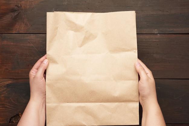 Dwie ręce trzyma papierową torbę brązowego papieru kraftowego nad drewnianym stołem