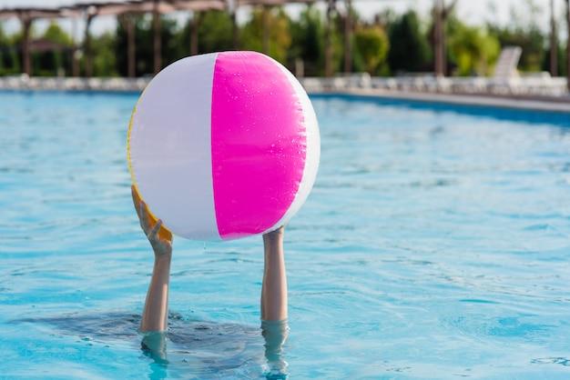 Dwie ręce trzymają nadmuchiwaną piłkę w basenie