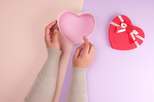 Dwie ręce trzymają otwarte na papierze czerwone pudełko w kształcie serca na fioletowym tle
