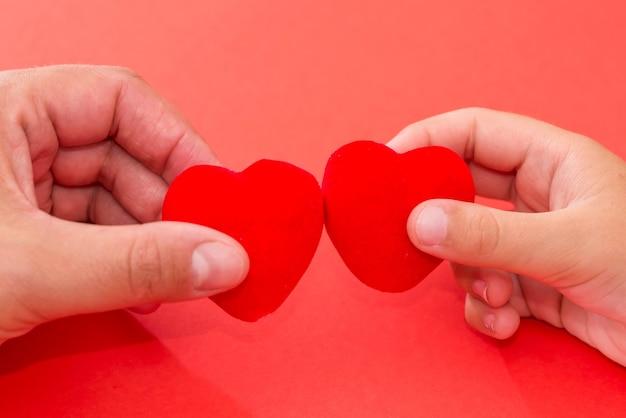 Dwie ręce trzymając czerwone serca na czerwonym tle, zdrowie serca, darowizna, koncepcja csr, światowy dzień serca, zdrowie, dzień rodziny, walentynki