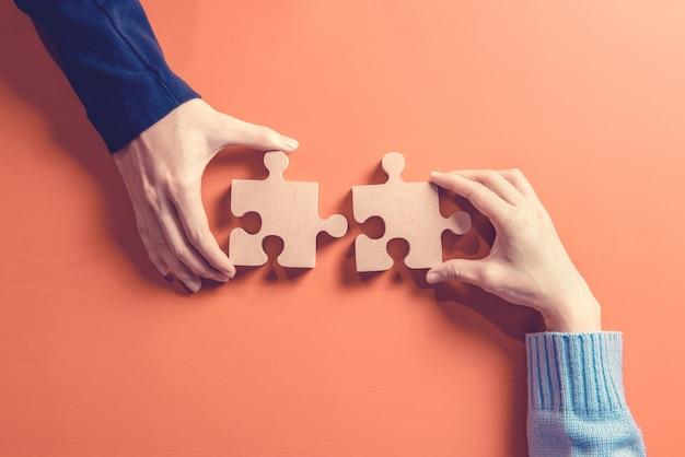 Dwie ręce trzymając układankę, koncepcja pracy zespołowej budowanie sukcesu.