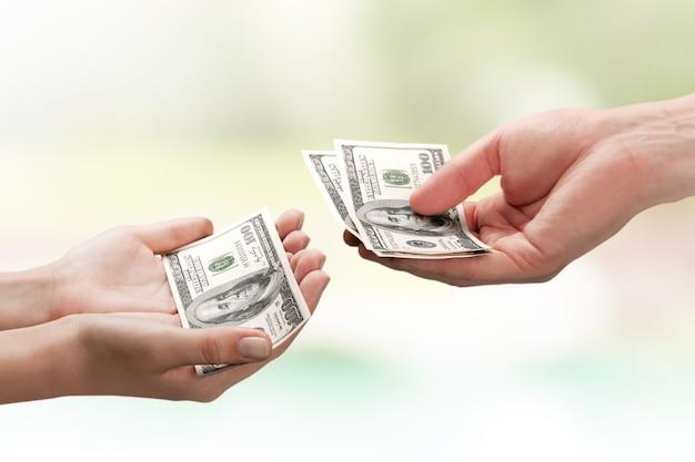 Dwie ręce trzymające banknot dolarów na tle