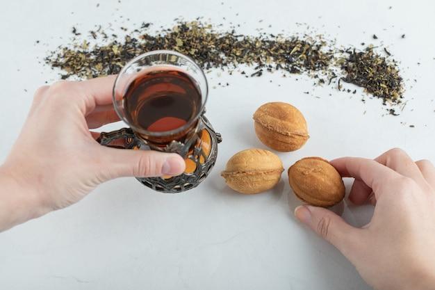 Dwie ręce trzymające filiżankę herbaty ziołowej i słodkie ciasteczko w kształcie orzecha włoskiego.