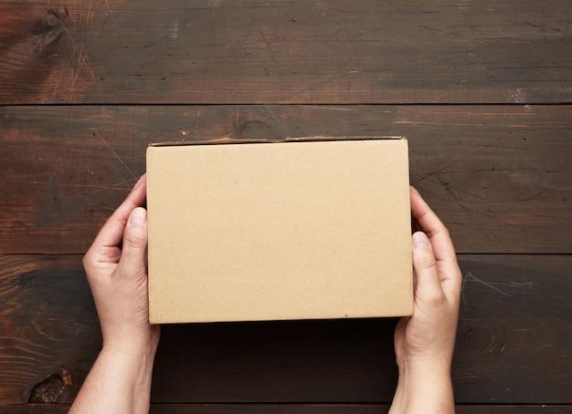 Dwie ręce trzymające prostokątne kartonowe pudełko z brązowego papieru pakowego