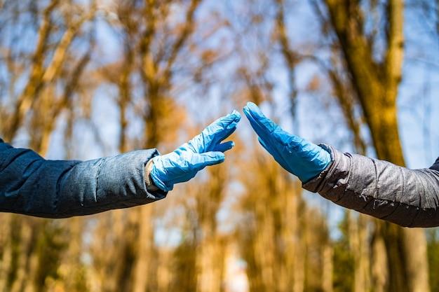 Dwie ręce w gumowych rękawiczkach medycznych. romantyczne relacje między ludźmi. ochrona, izolacja i odległość podczas pandemii koronawirusa covid-19.