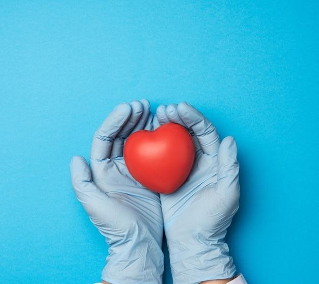 Dwie ręce w niebieskich rękawiczkach lateksowych, trzymając czerwone serce, koncepcja darowizny, widok z góry
