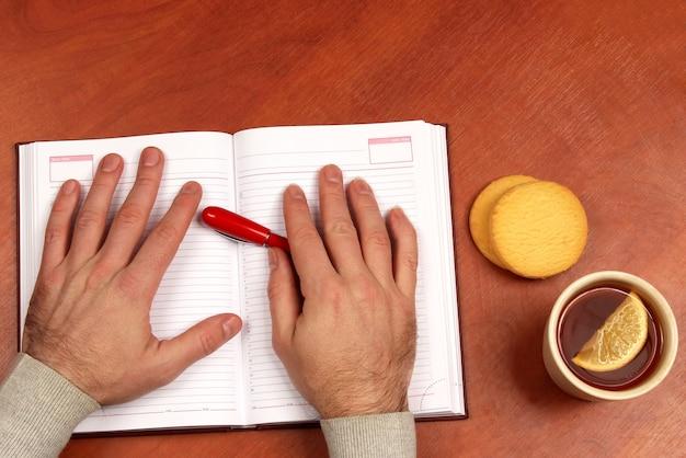 Dwie ręce z czerwonym długopisem leżące na notebooku na biurku z herbatą i ciastkami